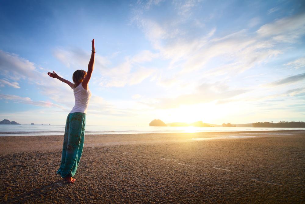 žena cvičí pozdrav slnku na pláži